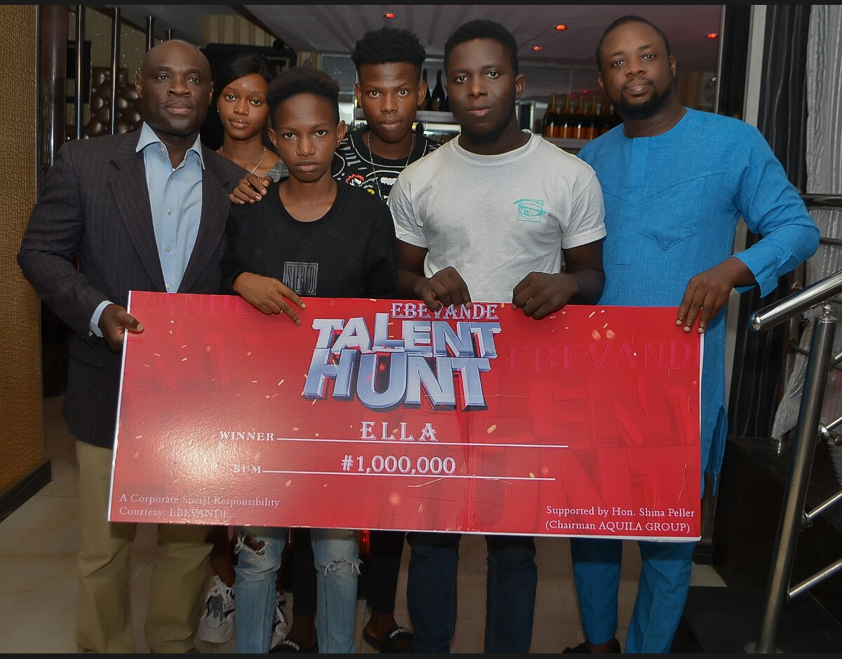 Honourable Oke and Ella with her friends receiving her dummy cheque for the N1mn prize