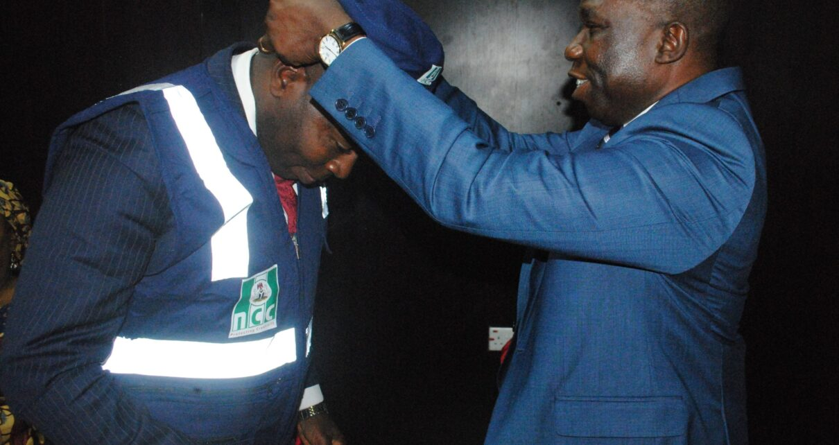 DG NCC, Mr. John O. Asein, decorates the NCC Board Chairman, Dr. Tonye Clinton Jaja, with the Enforcement Jacket of the Commission during his investiture as a Special Copyright Inspector in Abuja.